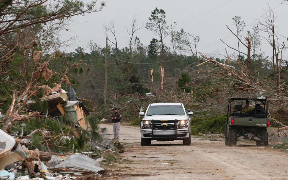 Damage from storms that killed at least 23 people is seen as Lee County deputies secure the scene in Beauregard.