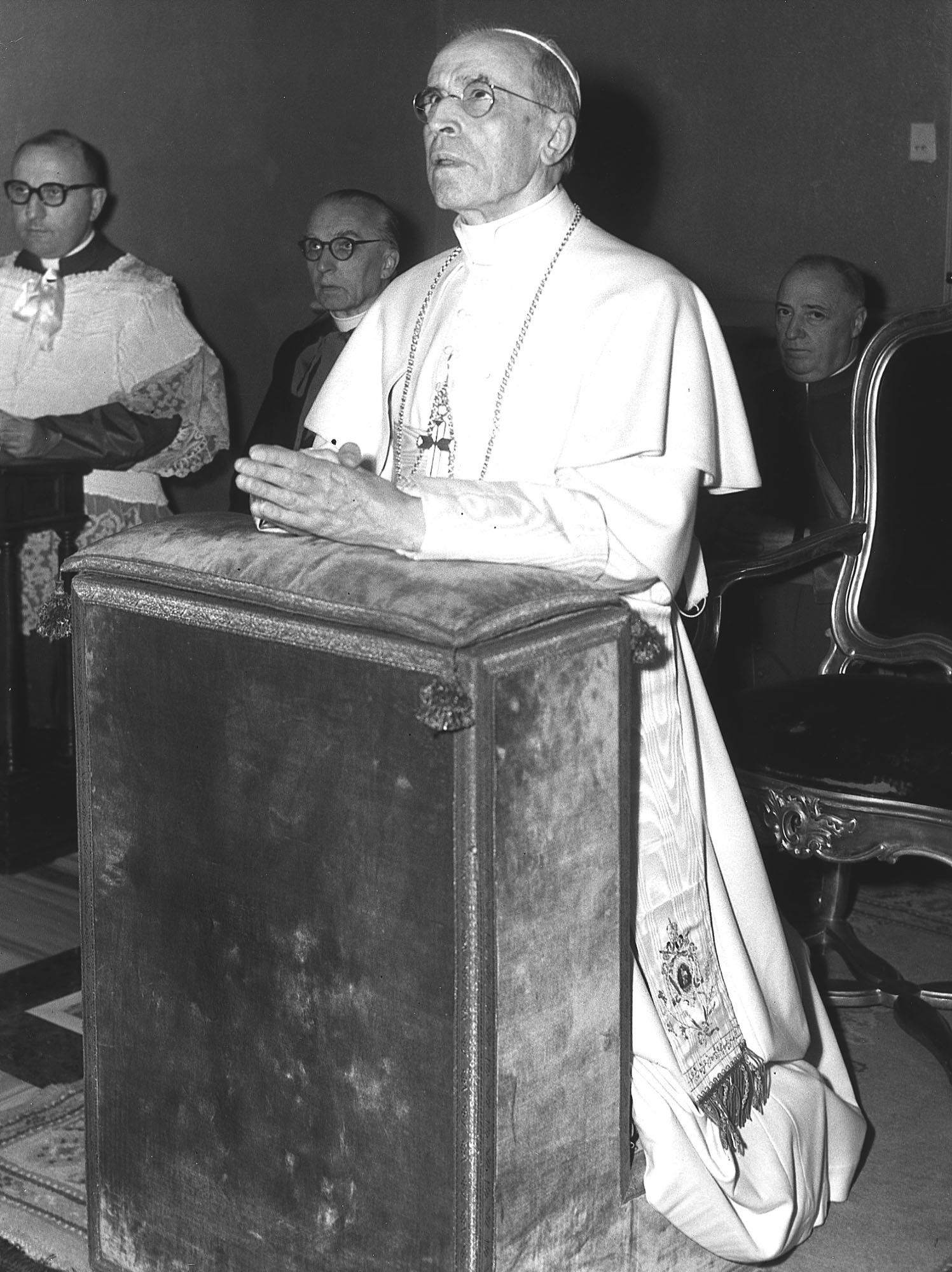 Pope Pius XII praying in his private chapel of the Papal summer residence at Castelgandolfo, about 17 miles south of Rome, Okt. 05, 1958. Sitting in background are (l/r:) Msgr. Mario Aluffi, chaplain of the Papl villa; and Msgr. Mario Nasalli Rocca, secret waiter to the Pontiff. The Pope was still today under treatment for gastritis and hiccups, the ailment that dangerously weakened him four years ago. The present affliction was described as a slight attack and does not cause undue concern, but precautions are taken both because of the Pontiff's advanced age and because of a fatigue, resulting from two months of intensive work. (AP-Photo/jo/Luigi Felici)