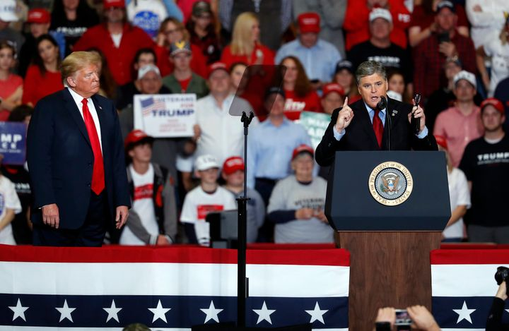 Television personality Sean Hannity, right, speaks as President Donald Trump listens during a campaign rally Monday, Nov. 5,