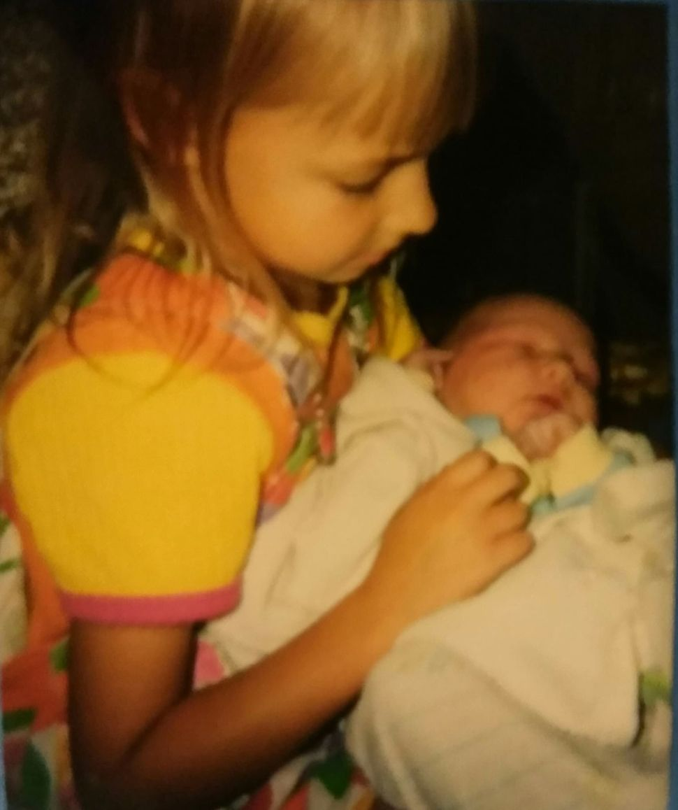 Jeub, age 5, holding baby No. 6, Micah, after a home birth in Kent, Minnesota, in 1997.