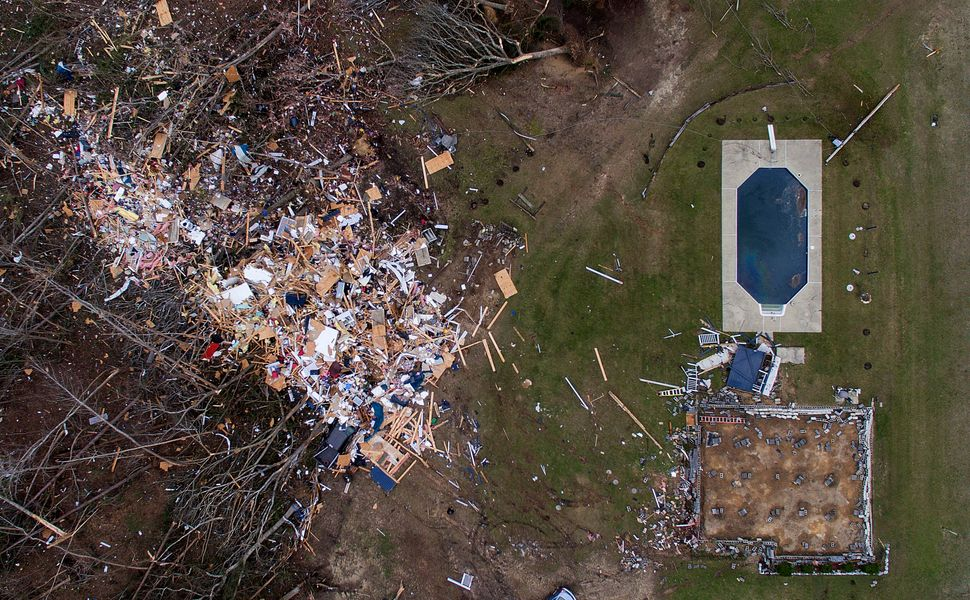 Debris from a home litters a yard the day after a tornado blew it off its foundation, lower right, in Beauregard, Alabama.