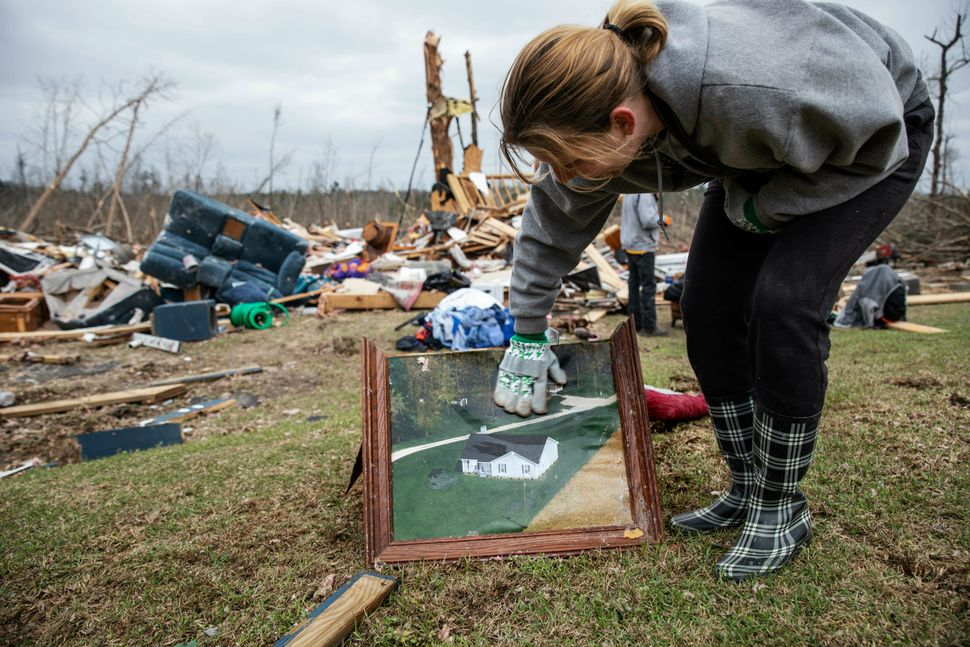 Debris from a friend's home stands in the background as Ashley Griggs wipes away dirt from a photo found in the rubble of wha