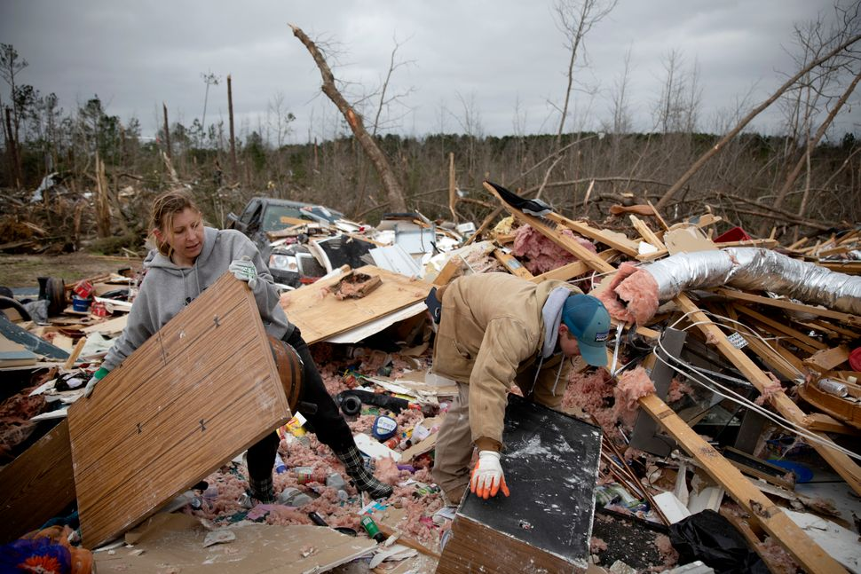 Ashley Griggs, left, helps Joey Roush sift through what is left of his mother's home after it was destroyed by the tornado.