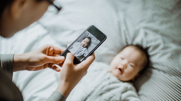 Mother photographing her baby girl with mobile phone. Photo Credit: Getty Images