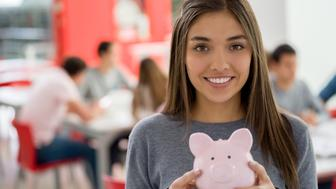 Beautiful female student at the library holding a piggy bank looking at camera smiling - Student loan concepts