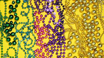 Assorted colors and types of mardi gras beads on yellow background arranged in color blocked pattern