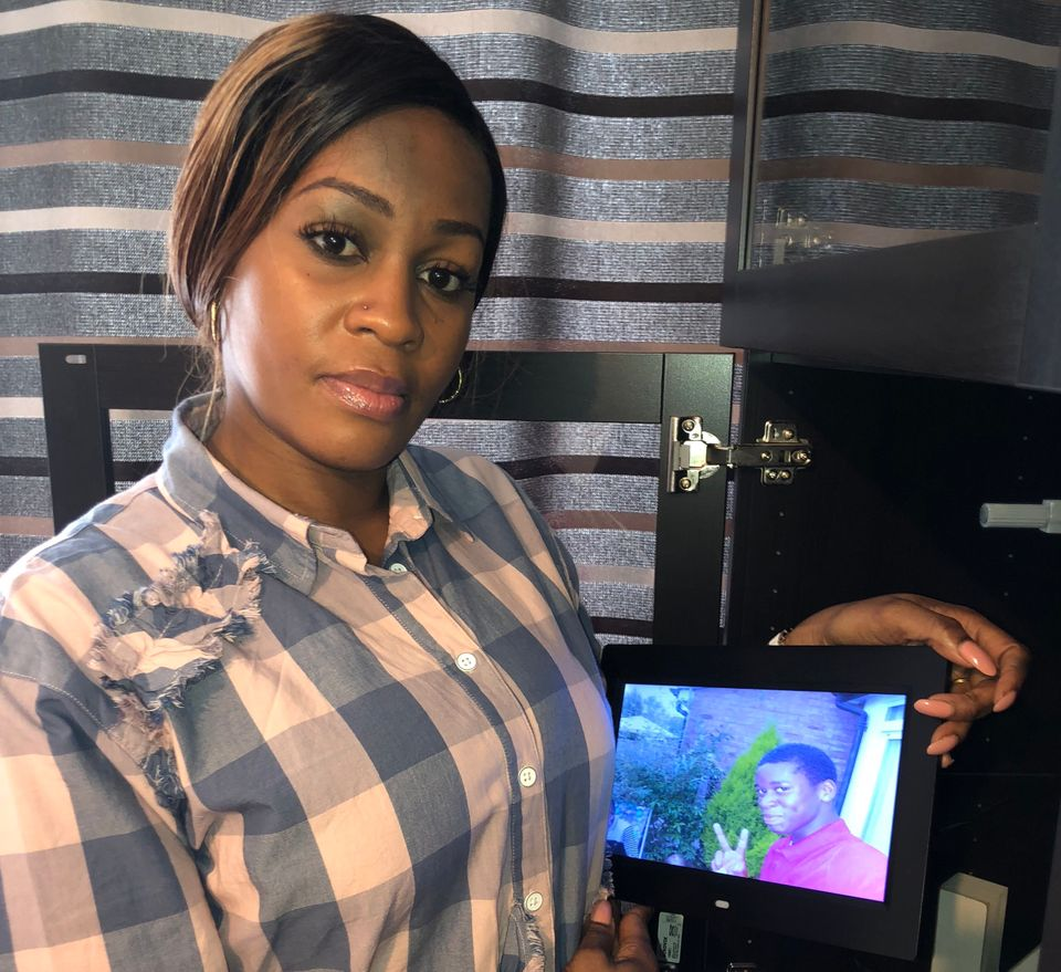 Peguy Kato holding a photograph of her son Champion, who was stabbed to death in