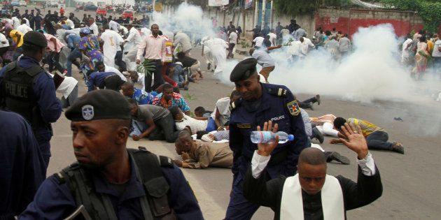 Riot policemen fire tear gas to disperse Catholic priest and demonstrators during a protest against President...