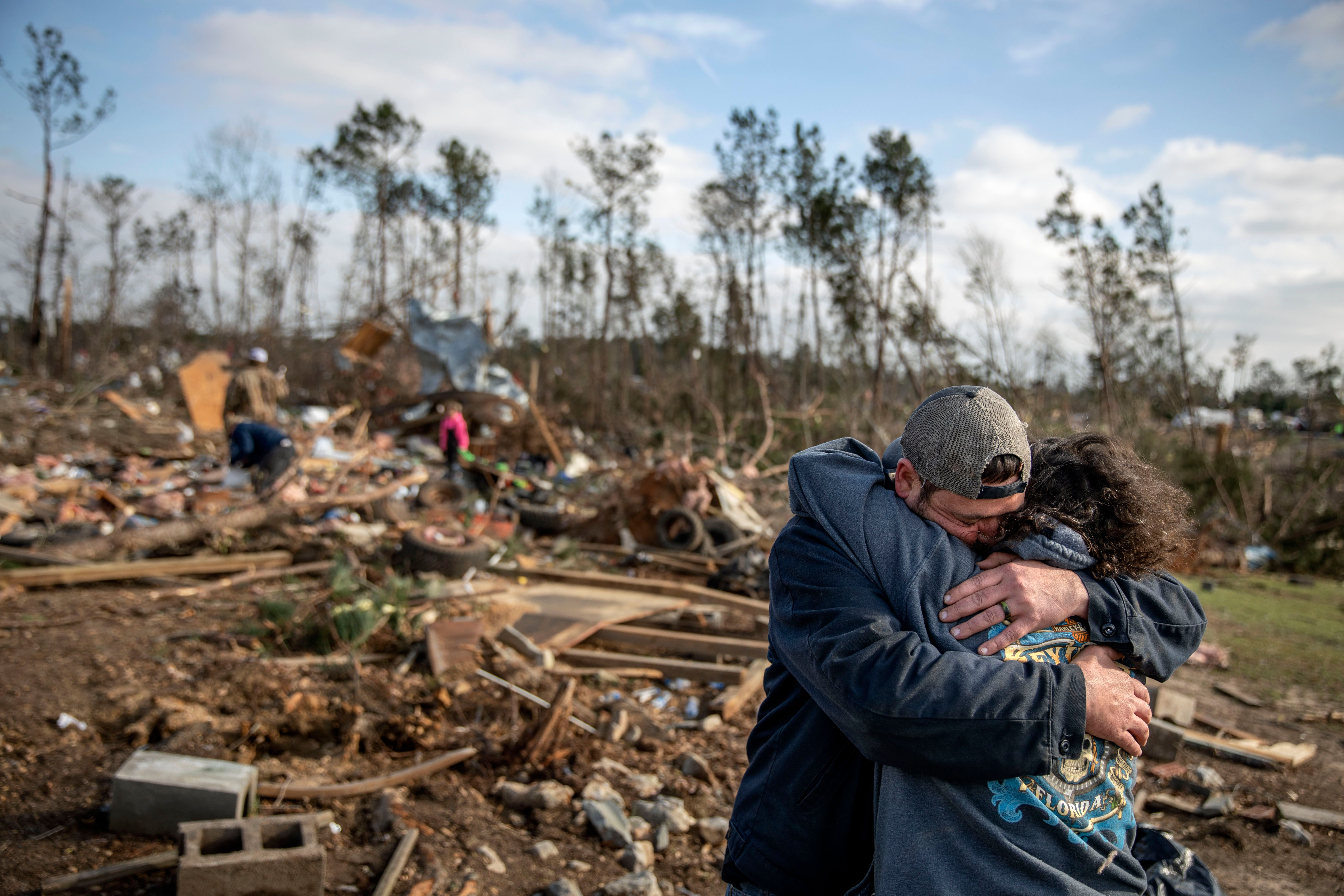 "ADDED SHARED WITH-Carol Dean, right, is embraced by David Theo Dean as they sift through the debris of the home Carol shared with her husband and David's father, David Wayne Dean, who died when a tornado destroyed the house in Beauregard, Ala., Monday, March 4, 2019. ""He was my wedding gift,"" said Dean of her husband whom she married three years ago. ""He was one in a million. He'd send me flowers to work just to let me know he loved me. He'd send me some of the biggest strawberries in the world. I'm not going to be the same."" (AP Photo/David Goldman)"