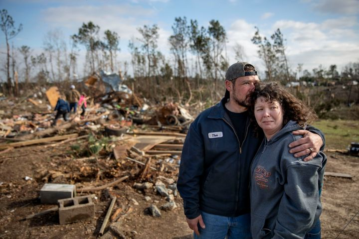 Carol Dean, right, is embraced by David Theo Dean as they sift through the debris of the home Carol shared her husband and Da