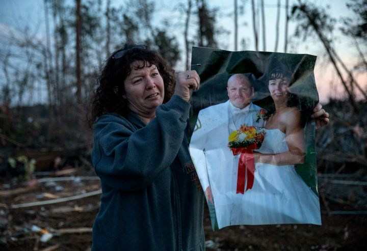 Carol Dean holds up her wedding photo to show family members after finding it in the rubble of the home she shared with husba