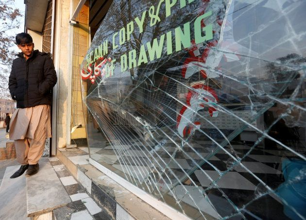 An Afghan shopkeeper looks at the broken glass window of his shop near the site of a bomb attack in Kabul,...