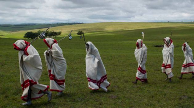 QUNU, EASTERN CAPE, SOUTH AFRICA, 14 DECEMBER 2013: Xhosa Initiates pass by close to the funeral of Nelson...