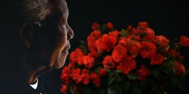 A posy of Mandela roses placed in front of a portrait of Nelson Mandela by the Nelson Mandela foundation,...