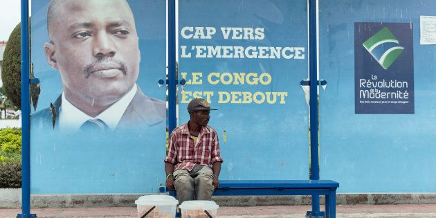 A vendor sits at a Kinshasa bus stop in front of a poster featuring the Democratic Republic of Congo