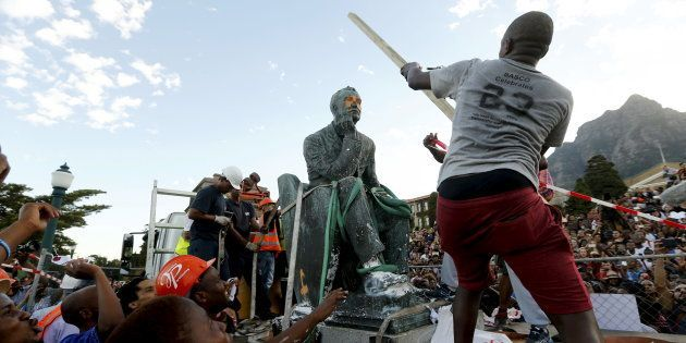 A student hits the statue of Cecil John Rhodes with a stick as it is removed from the University of Cape...
