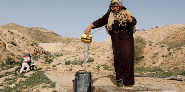 Saliha Mohamedi, 36, fills a bowl from her water storage outside her troglodyte