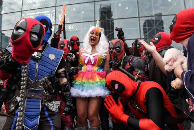 A woman dressed as a unicorn poses for a photograph with a group dressed as Deadpool during New York...