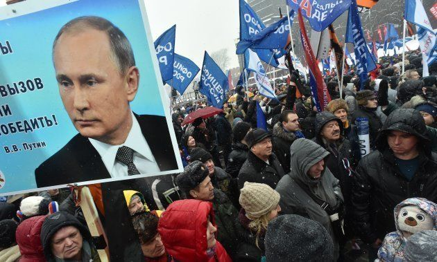 People hold a placard with the picture of Russian President Vladimir Putin and flags during the 'Russia...