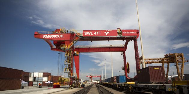 A loading crane straddles a freight rail track near shipping containers on the opening day of Transnet...