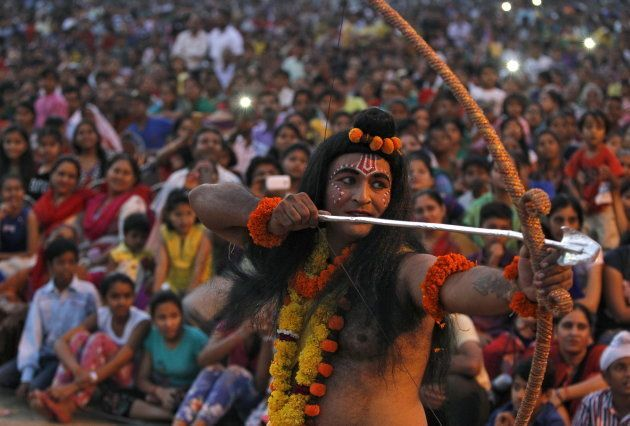 An artist dressed as Hindu God Rama acts in a religious play during Dussehra festival celebrations in...