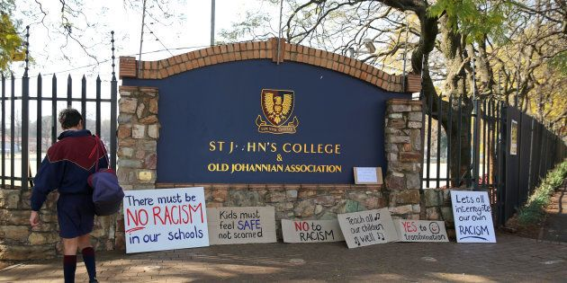 A student reads placards left at the entrance of the St. John's College in Johannesburg, South Africa,...