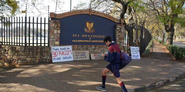 A student walks past placards left at the entrance of the St John's College in