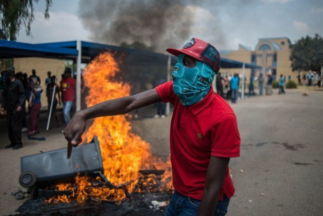 TOPSHOT - Students from Vaal University of Technology (VUT) shout slogans next to a burning barricade...