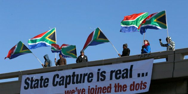 Protesters hang a banner as they hold flags in protest ahead of the African National Congress 5th National...