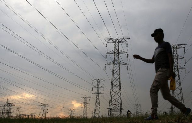 A man walks past electricity pylons in Soweto, South Africa, March 5, 2018. REUTERS/Siphiwe