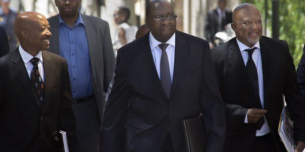 Minister of Finance Nhlanhla Nene (C), walks with Commissioner of the South African Revenue Service Tom...