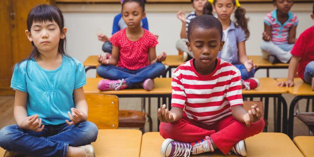 Pupils meditating in lotus position on desk in classroom at the elementary