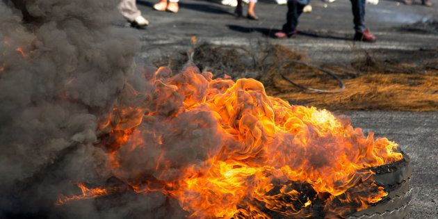 Protesters against the government burning rubber tyres in the streets in South