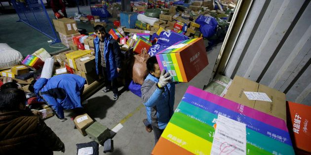 Workers move parcels at a logistic centre of ZTO Express during the Alibaba 11.11 global shopping festival,...