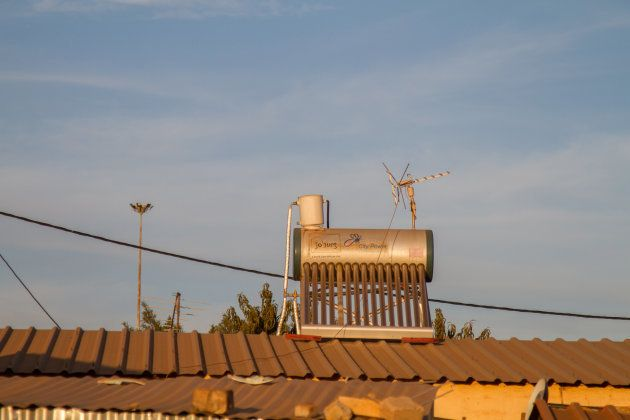 A solar water heater, manufactured by Jhb City Power, on the rooftop of a residential property in