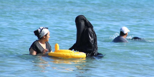 A woman wearing a niqab (C) cools off on the beach in Bizerte, Tunisia, July 21,