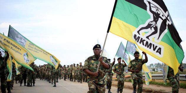 Members of the Umkhonto We Sizwe Military Veterans Association (MKMVA) hold flags as they arrive at the...