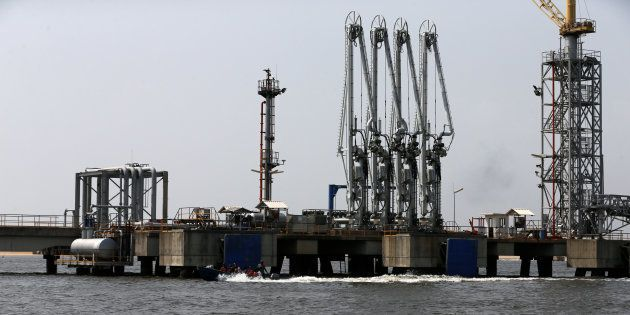 People ride a boat past an oil discharge facility that was damaged (not pictured) after militants from...