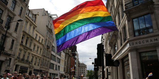 A rainbow flag is held aloft as the Pride in London parade makes its way through the streets of central,