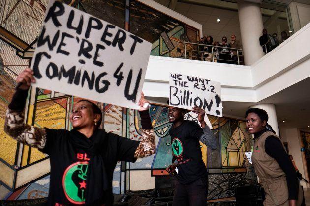 A placard with a slogan against Johann Rupert, the heir of South African business tycoon Anton Rupert,...