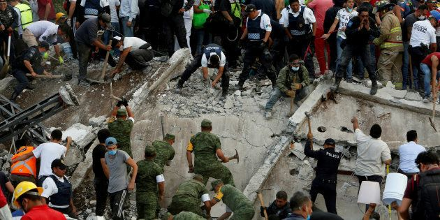 Soldiers, rescuers and people work at a collapsed building after an earthquake in Mexico City, Mexico...