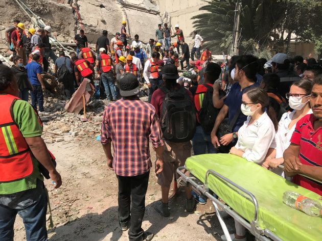 Paramedics get ready as people search the site of a collapsed building after an earthquake hit in Mexico...
