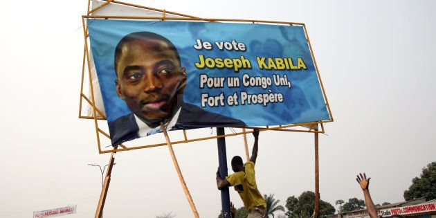 A Congolese protester tears down a campaign poster of President Joseph Kabila in Kinshasa, capital of...