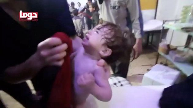 A child cries as they have their face wiped following alleged chemical weapons attack, in what is said...