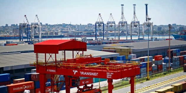 A crane operator unloads shipping containers from freight wagons at the Port of Durban, operated by Transnet...
