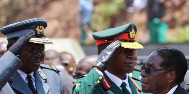 President Robert Mugabe arrives to address mourners gathered for the funeral of former cabinet minister...