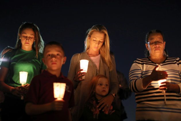 People pray during a candlelight vigil for victims of the Route 91 music festival mass shooting in Las...