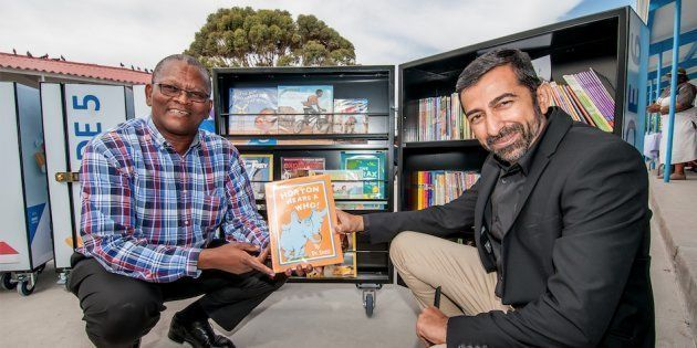 New Africa Education Foundation's Ahmed Motala (right) hands over mobile libraries to the principal of...