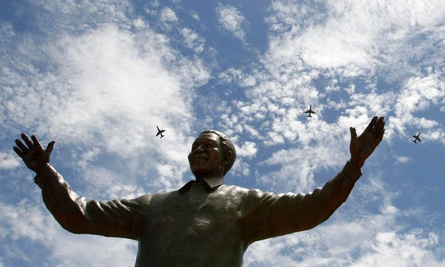 South African military jet fighters fly past a 9-metre (30-feet) bronze statue of the late former South...