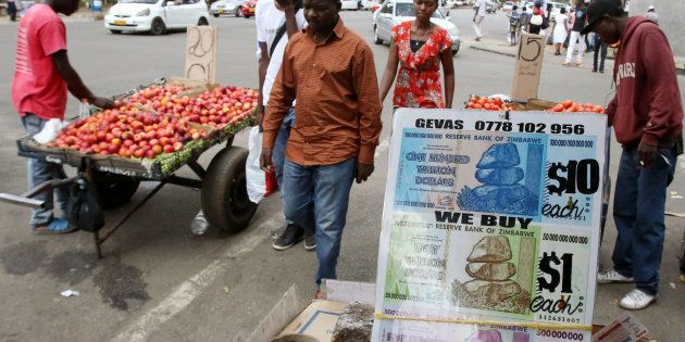 Locals walk past old currency notes on display along a street in the capital Harare, Zimbabwe, November...